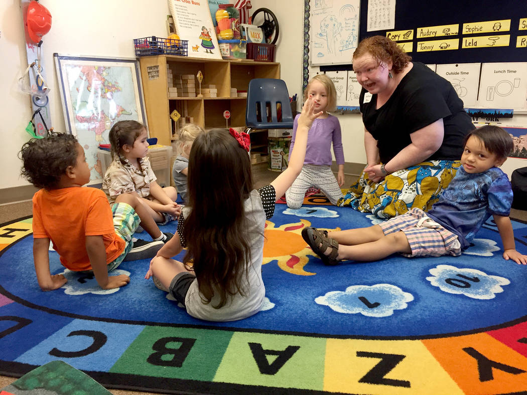 Rylan Standart, 4, raises her hand to answer a question  from Melissa Richardson during a storytelling exercise. Richardson, a professional teaching artist, is working with students and teachers a ...