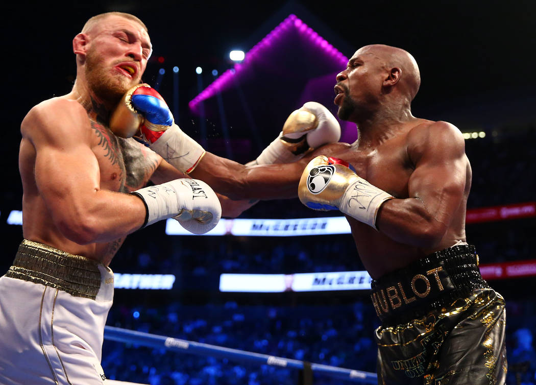 Floyd Mayweather Jr. lands a hit against Conor McGregor during a boxing match at T-Mobile Arena. Mandatory Credit: Mark J. Rebilas-USA TODAY Sports