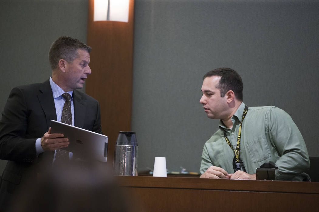 Peter S. Christiansen, left, attorney for murder suspect Assuan Martinez, shows an interview transcript to Las Vegas police Detective Christopher Grivas during his client's preliminary hearing at  ...