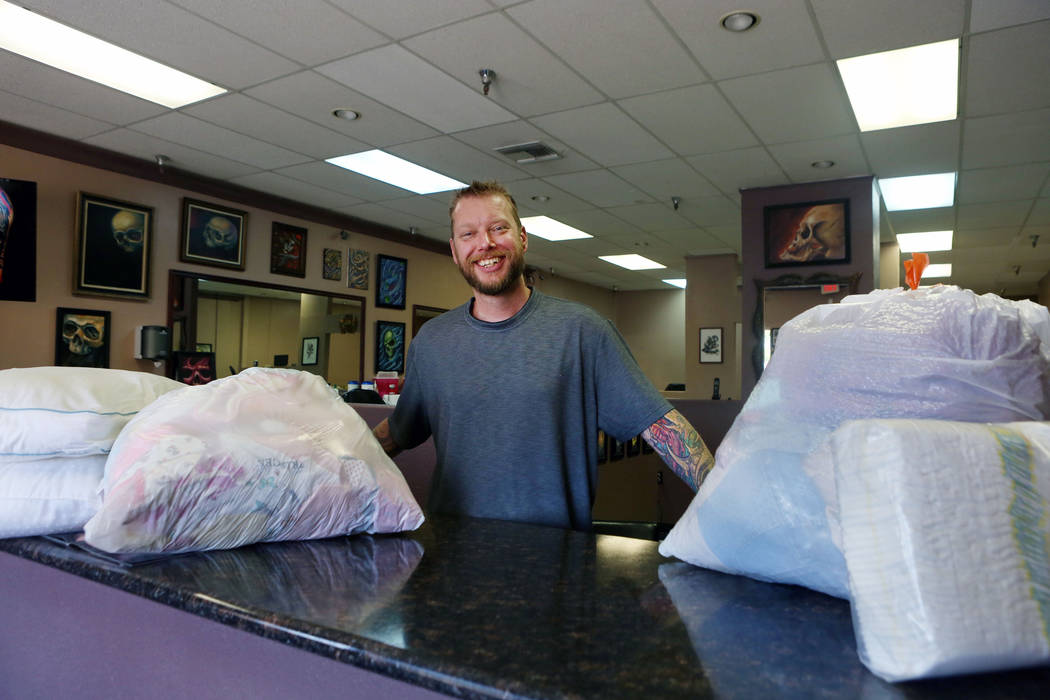Owner and artist Joe Riley of Inner Visions Tattoo with donated goods at his store in Las Vegas, Wednesday, Aug. 30, 2017. Riley will give away gift cards to those who donate, and will ship the do ...