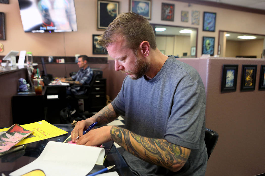 Owner and artist Joe Riley of Inner Visions Tattoo draws a tattoo at his store in Las Vegas, Wednesday, Aug. 30, 2017. Riley will give away gift cards to those who donate things like blankets, clo ...