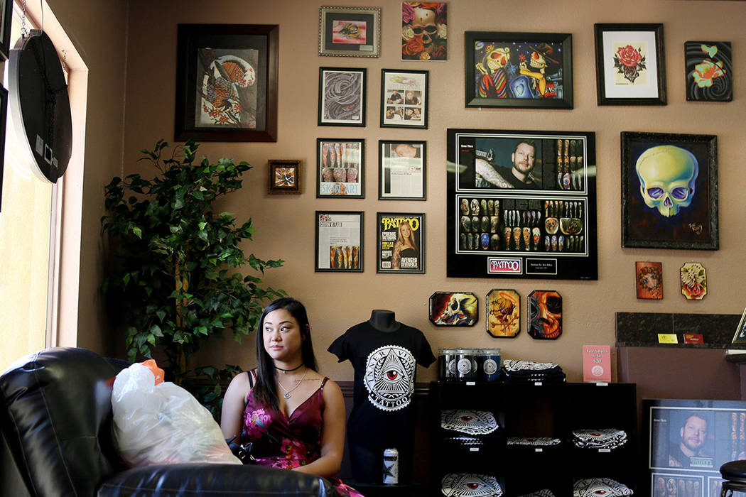 Emy Tolentino waits for her tattoo appoint with her bag of baby clothes she is donating to Inner Visions Tattoo in Las Vegas, Wednesday, Aug. 30, 2017. Inner Visions will give away gift cards to t ...