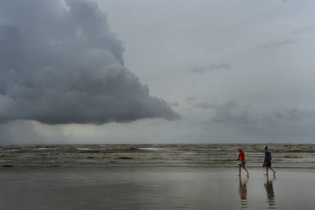A couple strolls along the shore in McFaddin Beach, Texas on Saturday, Aug. 26, 2017, as storm clouds build on the horizon the day after Hurricane Harvey made land, battering the gulf communities  ...