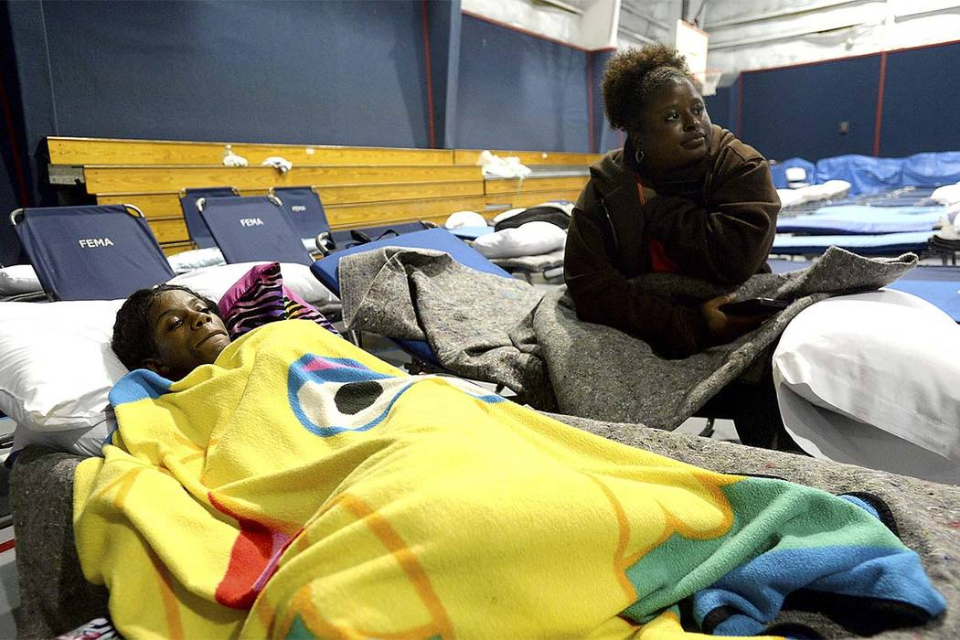 Kori'yana Lyons (left) and Phyllis Moore rest on their cots at the Salvation Army in Beaumont Tuesday, Aug. 29, 2017. While these women were rescued, another woman In Beaumont wasn't as lucky as h ...