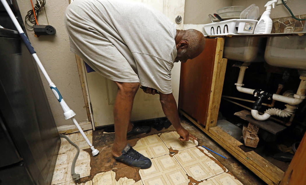 Clarence Johnson cleans up inside of his Lake Charles, La., home Tuesday, Aug. 29, 2017. Johnson, who was at home when the flood waters from Harvey, crept into his home ruined a stereo system, tel ...