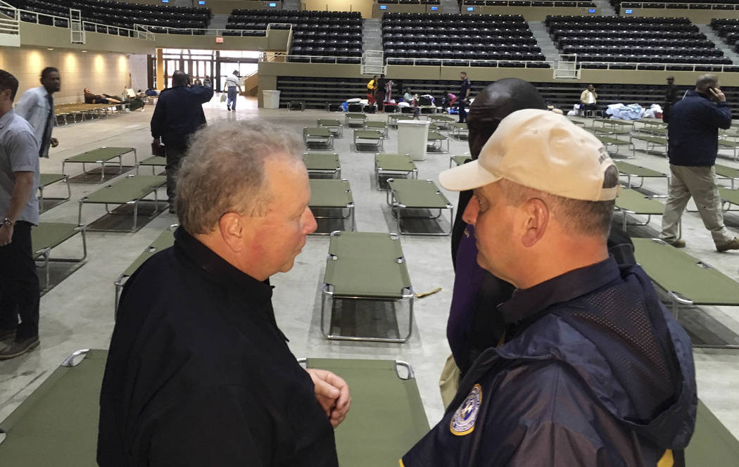 Dick Gremillion, director of the office of Homeland Security and Emergency Preparedness for Calcasieu Parish, left, confers with Louisiana Gov. John Bel Edwards in the Lake Charles Civic Center sh ...