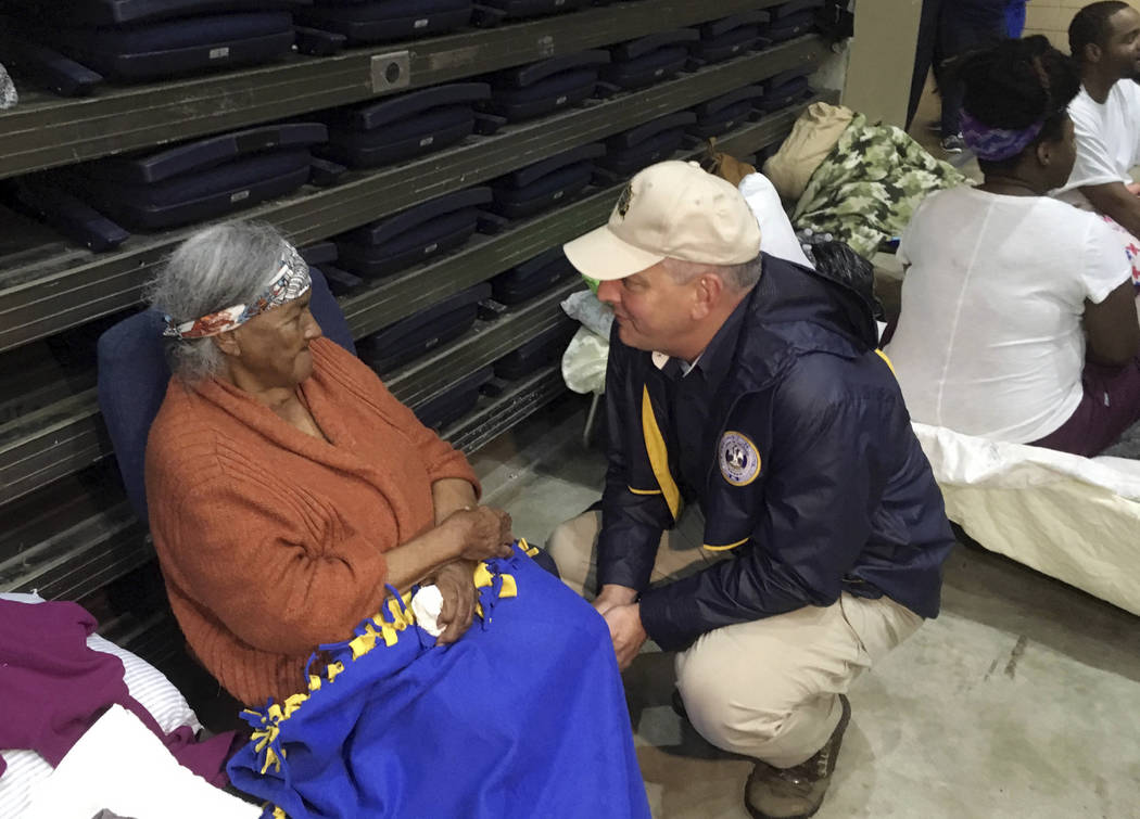 Louisiana Gov. John Bel Edwards, right, confers with a flood refugee in the Lake Charles Civic Center shelter, in Lake Charles, La., Tuesday, Aug. 29, 2017. Edwards spent some time speaking with a ...