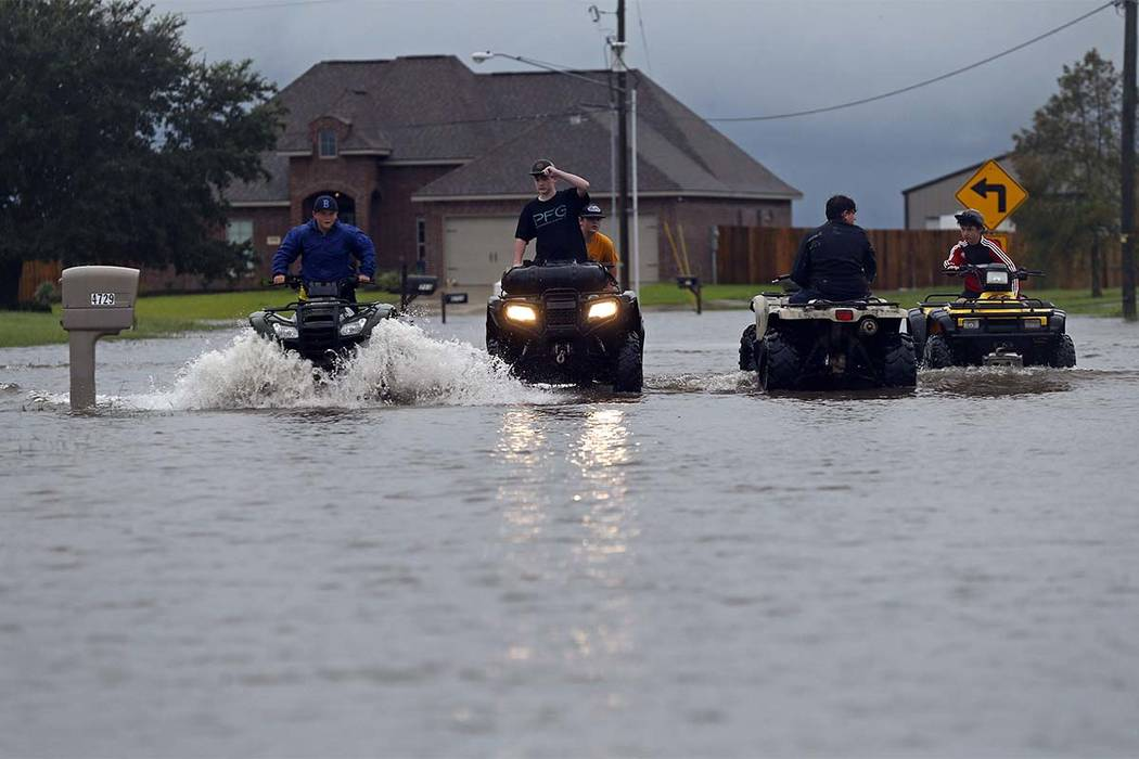 Kids ride an ATV in a street flooded by Tropical Storm Harvey, in the Clearfield Farm subdivision in Lake Charles, Louisiana, Tuesday, Aug. 29, 2017. (Gerald Herbert/AP)