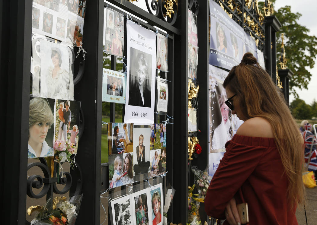 A woman looks at tributes and memorabilia for the late Diana, Princess of Wales outside Kensington Palace in London, Tuesday, Aug. 29, 2017. The tributes are placed on one of the ornamental gates  ...