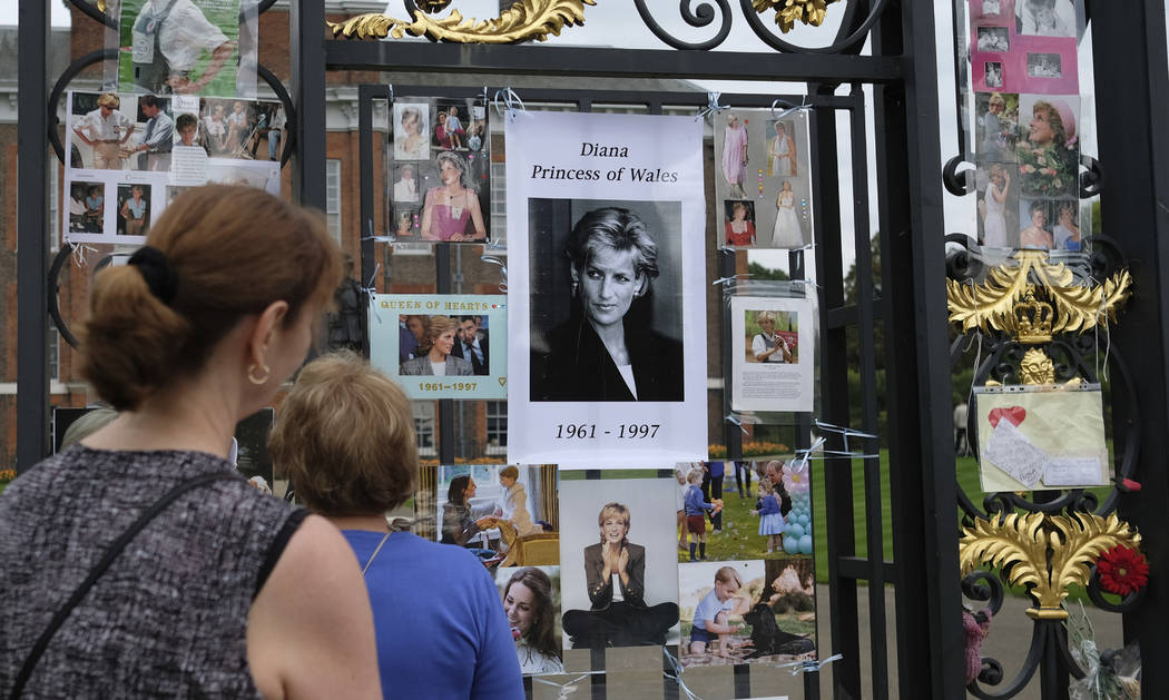 Tourists look at tributes and memorabilia for the late Diana, Princess of Wales outside Kensington Palace in London, Tuesday, Aug. 29, 2017. The tributes are placed on one of the ornamental gates  ...