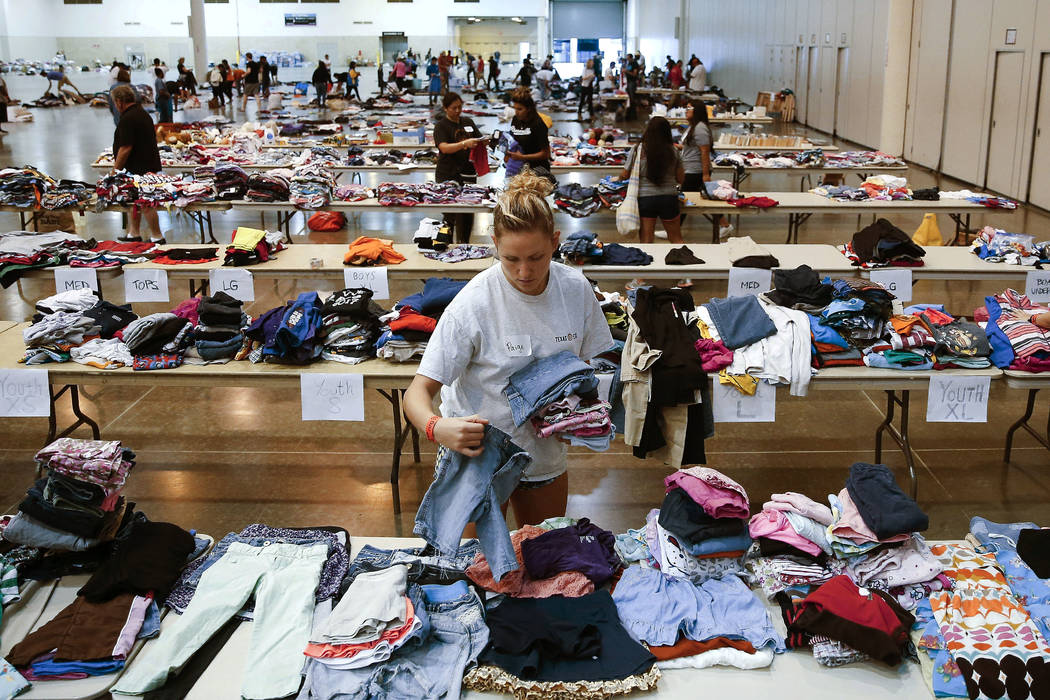 Volunteer Paige Atkinson sorts donated clothing at NRG Center, which opened its doors to  evacuees in the wake of Tropical Storm Harvey Wednesday, Aug. 30, 2017 in Houston. Officials say nearly al ...