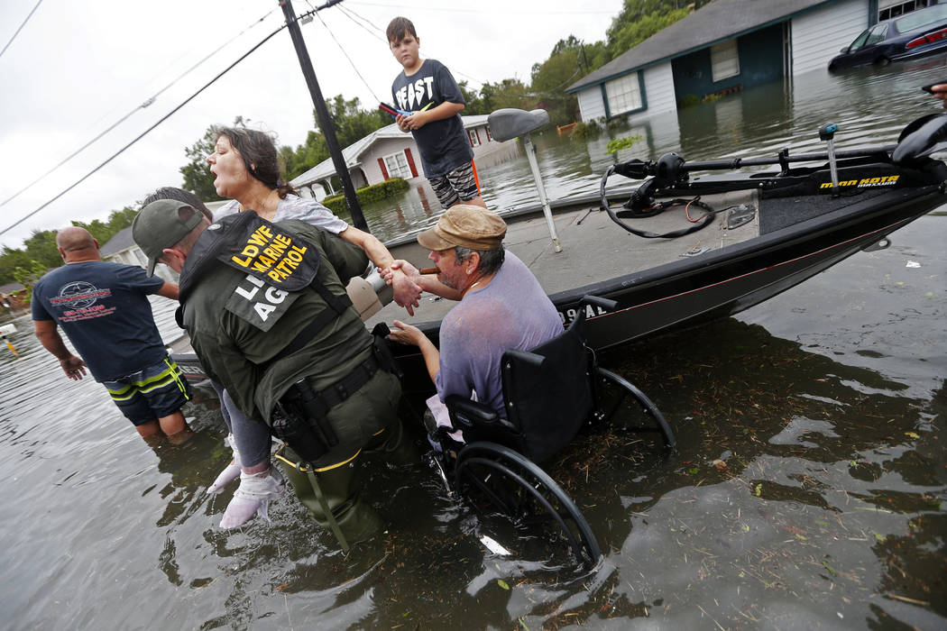 Members of the Louisiana Department of Wildlife and Fisheries help rescue Mike Henry, right, and his partner Rosemarie Carpenter during flooding from Tropical Storm Harvey in Orange, Texas, Wednes ...