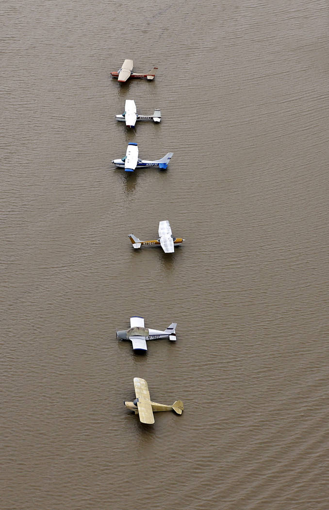Airplanes sit at a flooded airport near the Addicks Reservoir as floodwaters from Tropical Storm Harvey rise Tuesday, Aug. 29, 2017, in Houston. (David J. Phillip/AP)