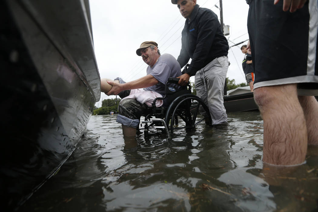 Mike Henry, center, lifts his leg onto a boat as members of the Louisiana Department of Wildlife and Fisheries helps rescue him during flooding from Tropical Storm Harvey in Orange, Texas, Wednesd ...