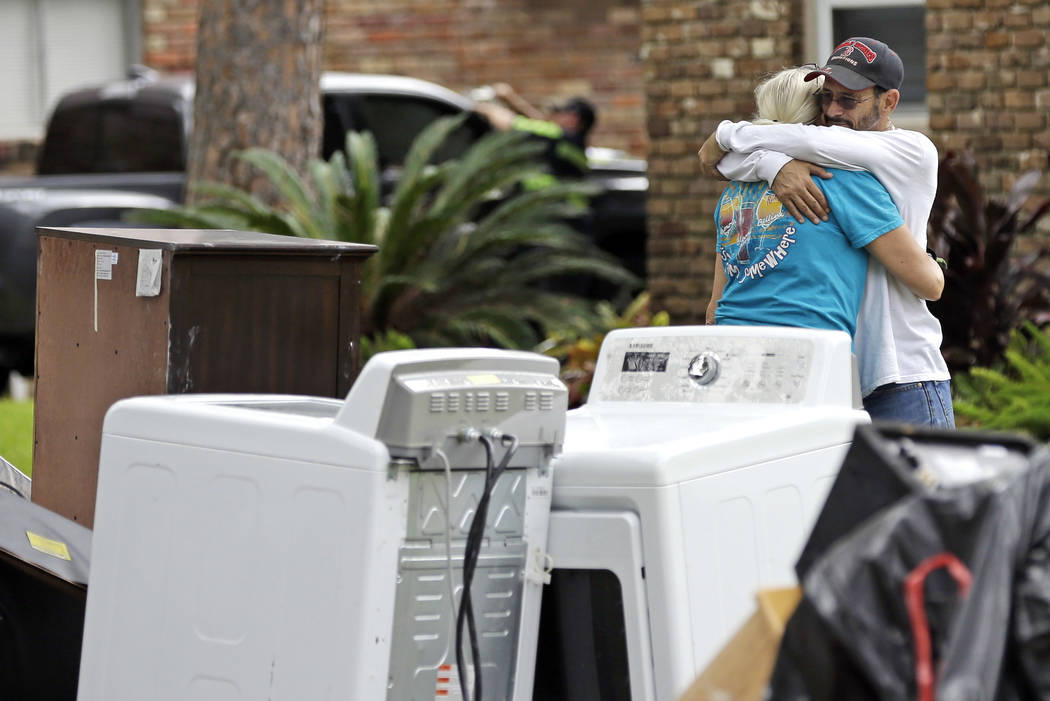 Barry Horvitz embraces his wife Kim while standing outside their home after removing items damaged by floodwaters from Tropical Storm Harvey on Wednesday, Aug. 30, 2017, in Houston. (David J. Phil ...