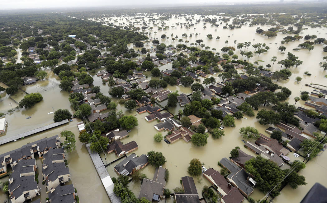 Water from Addicks Reservoir flows into neighborhoods as floodwaters from Tropical Storm Harvey rise Tuesday, Aug. 29, 2017, in Houston. (David J. Phillip/AP)