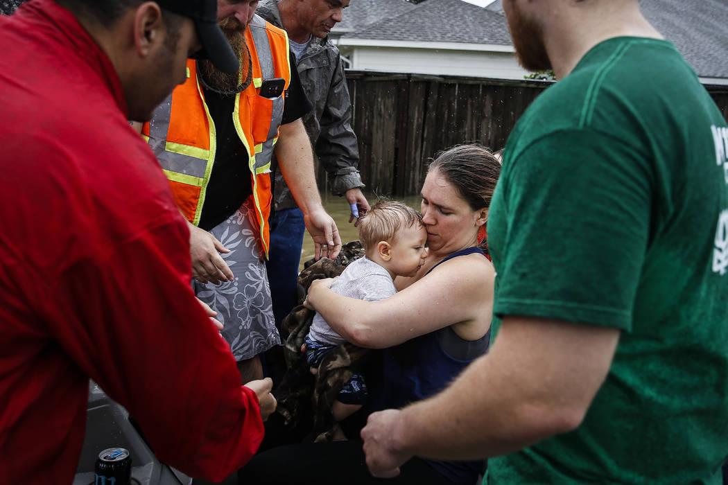 Lauren Durst holds onto her ten-month-old son, Wyatt Durst, as they evacuate from the Savannah Estates neighborhood as Addicks Reservoir nears capacity during Tropical Storm Harvey, Tuesday, Aug.  ...