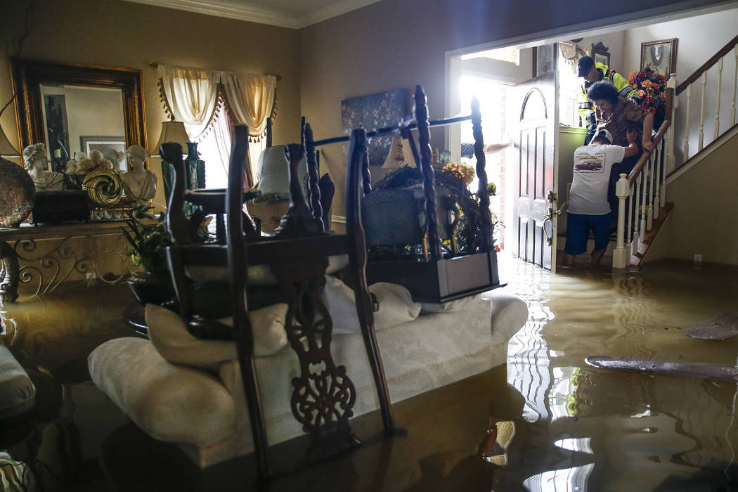 Chris Gutierrez, second from right, helps his grandmother, Edelmira Gutierrez, down the stairs of their flooded house and into a waiting fire department truck in the Concord Bridge neighborhood as ...