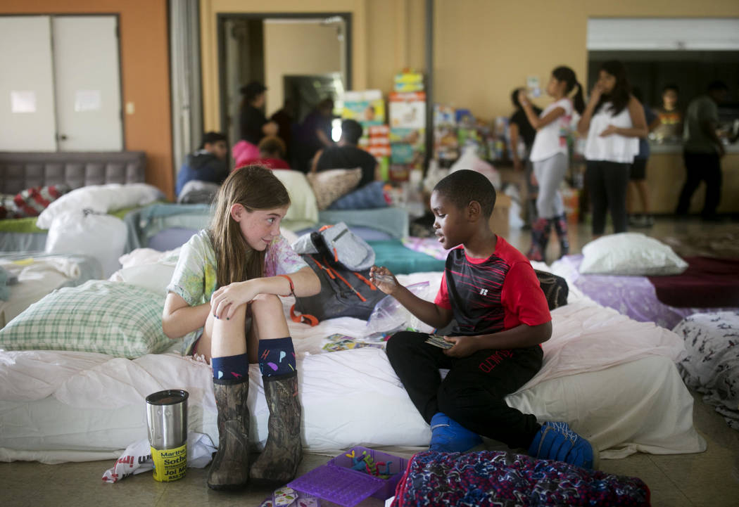 Volunteer Elizabeth Hill, 8, plays with evacuee Skyler Smith, 7, at a shelter at St. Thomas Presbyterian Church in west Houston as Tropical Storm Harvey continues to affect the area Tuesday, Aug.  ...