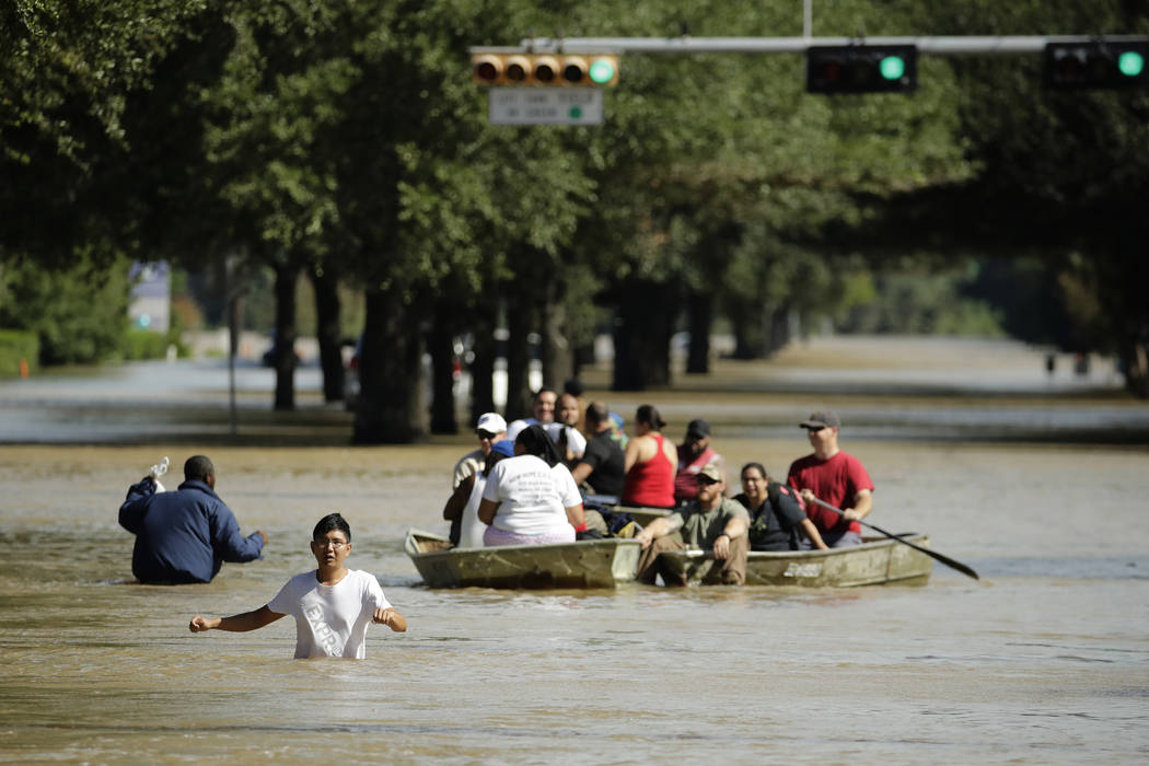 People evacuate a neighborhood inundated after water was released from nearby Addicks Reservoir when it reached capacity due to Tropical Storm Harvey on Wednesday, Aug. 30, 2017, in Houston. (Char ...