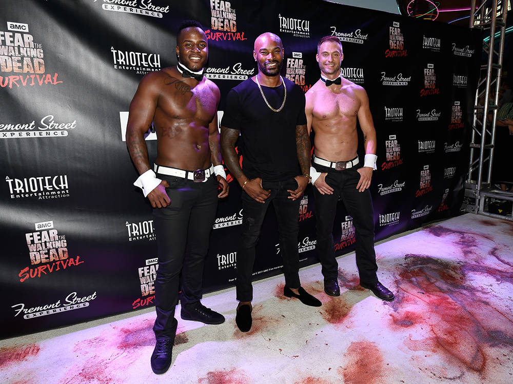 "Chippendales dancer Okewa Garrett, left, Tyson Beckford, and Chippendales dancer James David arrive at the grand opening of downtown Las Vegas' newest entertainment destination, ""Fear The Walking  ..."