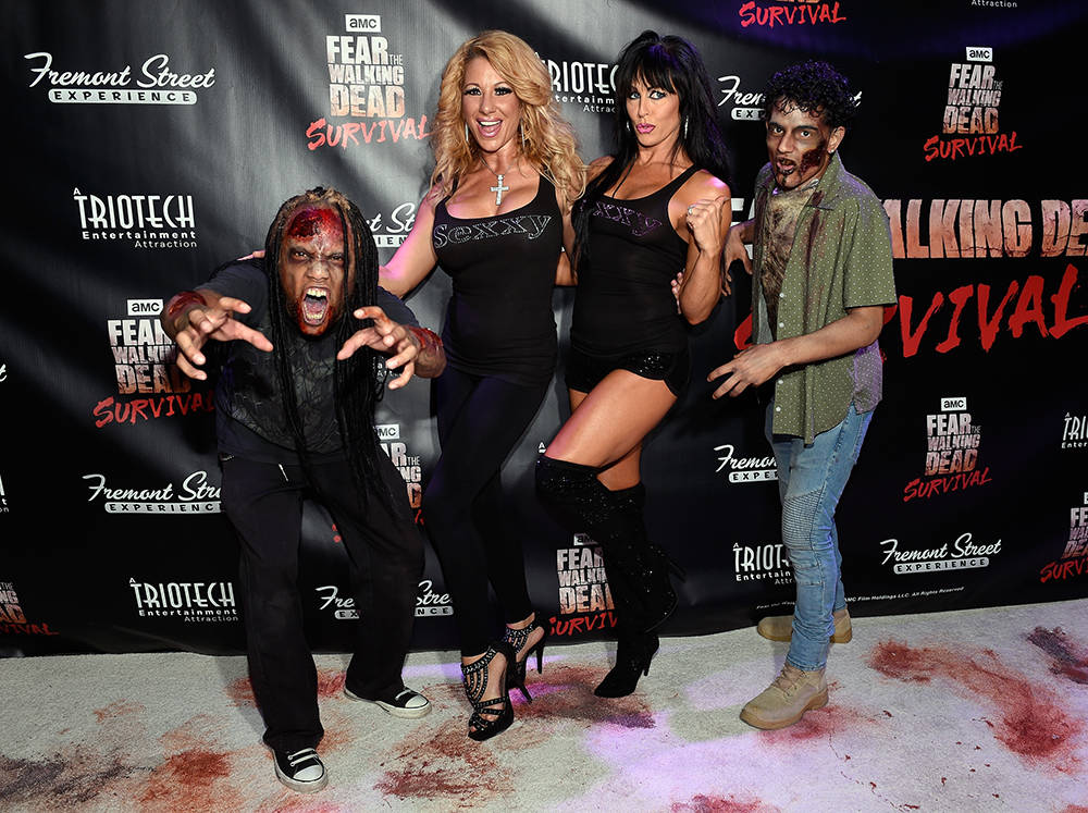 "Entertainers Gabriella Versace, second left, and Jennifer Romas arrive at the grand opening of downtown Las Vegas' newest entertainment destination, ""Fear The Walking Dead Survival."" (David Becker ..."