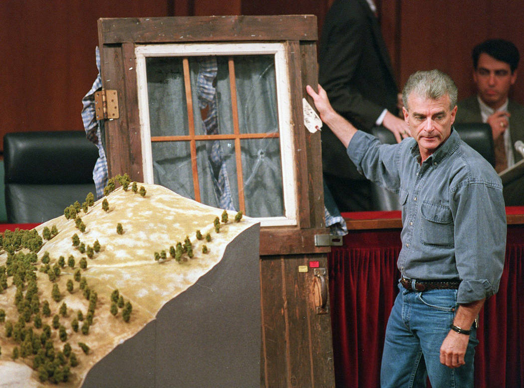 Randy Weaver holds the door of his cabin showing holes from bullets fired during the 1992 siege of his Ruby Ridge, Idaho, home, model at left, during testimony Sept. 6, 1995, before the Senate Jud ...