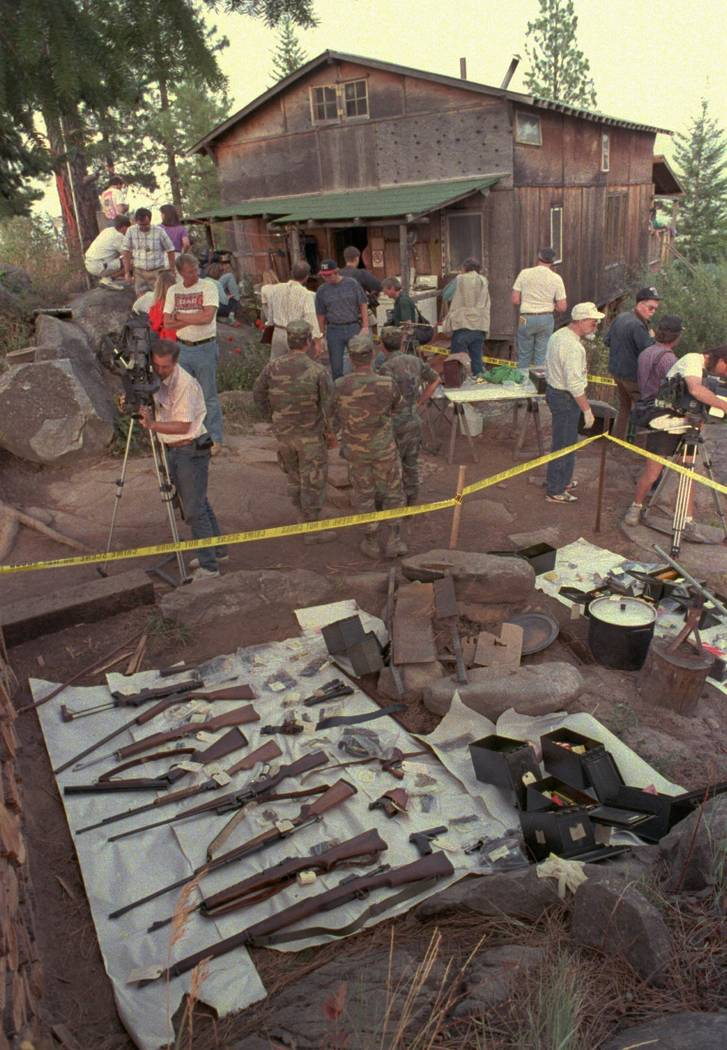 Media members and federal agents tour the outside of Randy Weaver's home near Naples, Idaho, Sept. 1, 1992. (Gary Stewart, File, AP)