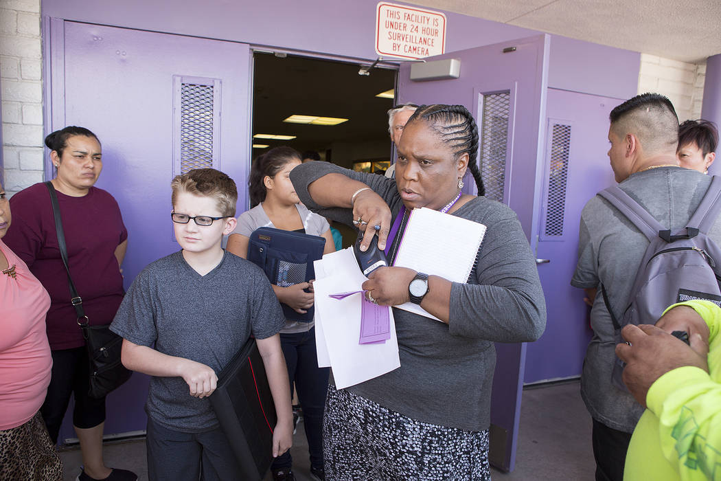 Dean of students Valencia Meyer releases a small amount of students to parents and guardians that are present at Dell H. Robison Middle School on Wednesday, Aug. 30, 2017. Bridget Bennett Las Vega ...