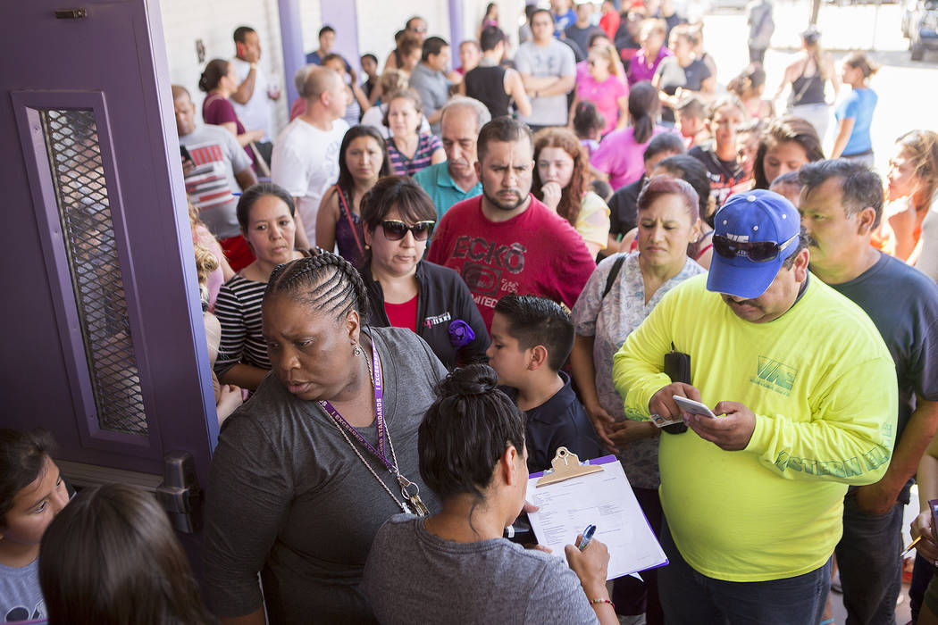 Dean of students Valencia Meyer, lower left, releases a small amount of students to parents and guardians that are present at Dell H. Robison Middle School on Wednesday, Aug. 30, 2017. Bridget Ben ...