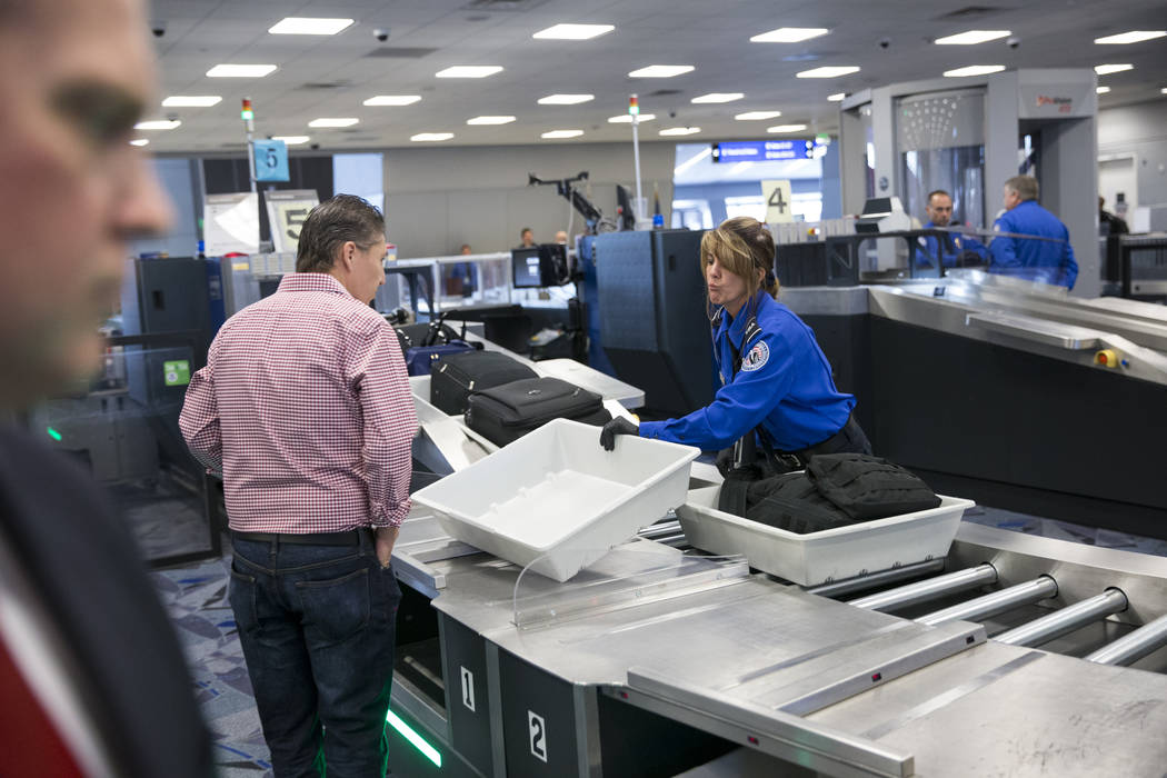 Transportation Security Administration agent Donna Franco, right, assists a passenger in one of the new automated screening lanes at McCarran International Airport Terminal 1 in Las Vegas, on Thur ...