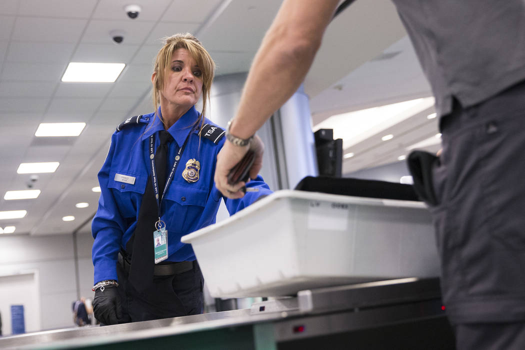 Transportation Security Administration agent Donna Franco assists a passenger in one of the new automated screening lanes at McCarran International Airport Terminal 1 in Las Vegas, on Thursday, Au ...