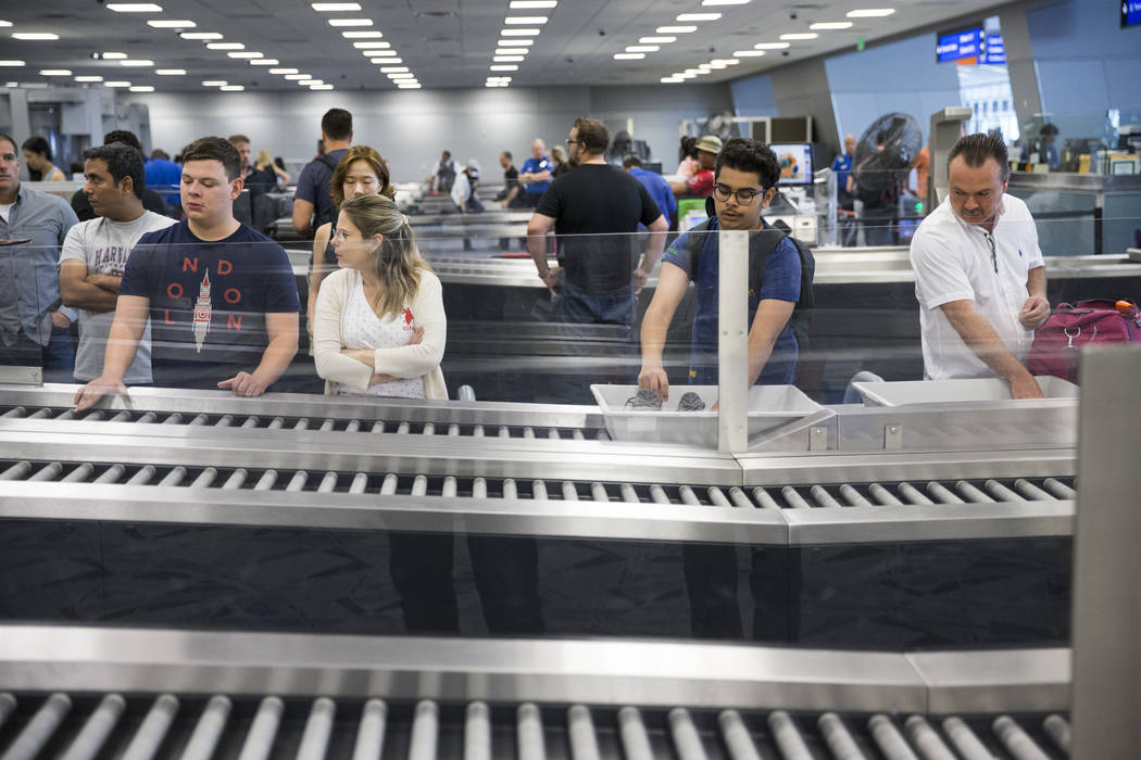 Passengers wait to retrieve their belonging from one of the new automated screening lanes at McCarran International Airport Terminal 1 in Las Vegas, on Thursday, Aug. 31, 2017. Erik Verduzco Las V ...