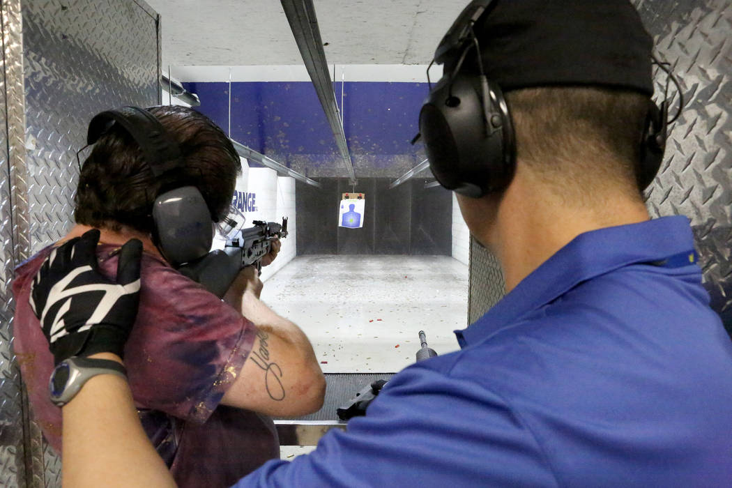 Adam Miller of Tampa, Fla., left, takes aim with an AK-47 assault rifle at The Range 702 on Monday, Aug. 28, 2017. (Michael Quine/Las Vegas Review-Journal) @Vegas88s