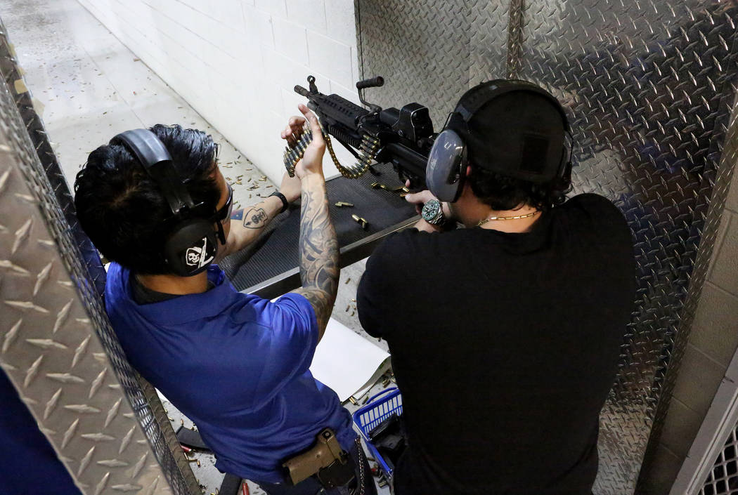 Range Safety Officer Henston Hortillosa, left, feeds an ammo belt into an M249 SAW submachine for Horacio Gonzalez, 32, of Venezuela at The Range 702 on Monday, Aug. 28, 2017. (Michael Quine/Las V ...