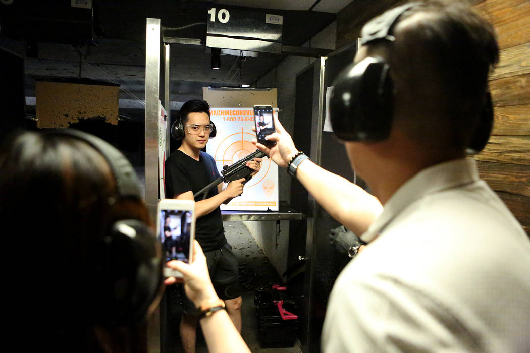Daniel Sun from Singapore holds up an MP5 submachine gun for friends Angela Xuan, left, and Jeff Kuah to photograph after firing it at Machine Guns Vegas on Wednesday, Aug. 30, 2017. (Michael Quin ...