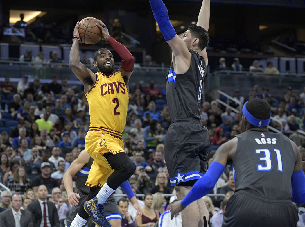 FILE - In this March 11, 2017, file photo, Cleveland Cavaliers guard Kyrie Irving (2) looks to pass in front of Orlando Magic forward Terrence Ross (31) and center Nikola Vucevic during an NBA bas ...