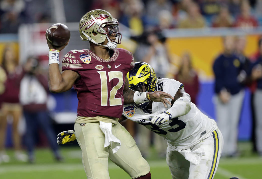 Florida State quarterback Deondre Francois (12) looks to pass under pressure from Michigan defensive end Taco Charlton (33), during the second half of the Orange Bowl NCAA college football game, F ...