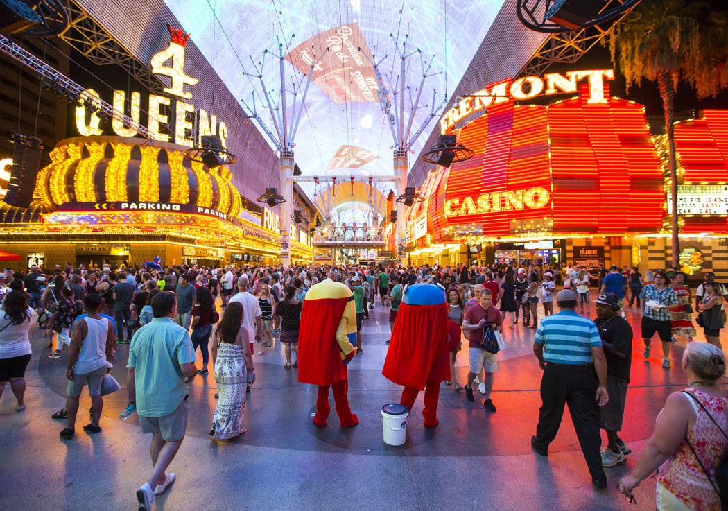 "Buskers dressed as characters from ""Minions"" wait to pose with tourists for tips along the Fremont Street Experience in downtown Las Vegas on Wednesday, Aug. 2, 2017. Chase Steve ..."