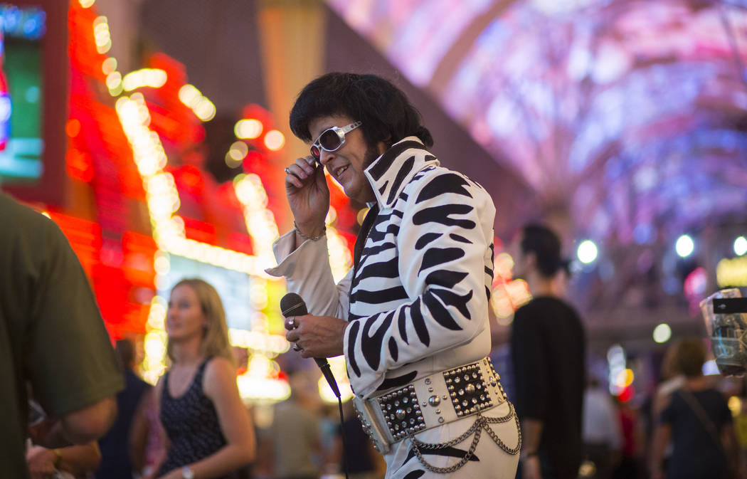 Chris Johnson, dressed as Elvis, is one of many costumed buskers offering photo opportunities along the Fremont Street Experience in downtown Las Vegas on Tuesday, Aug. 1, 2017. Chase Stevens Las  ...