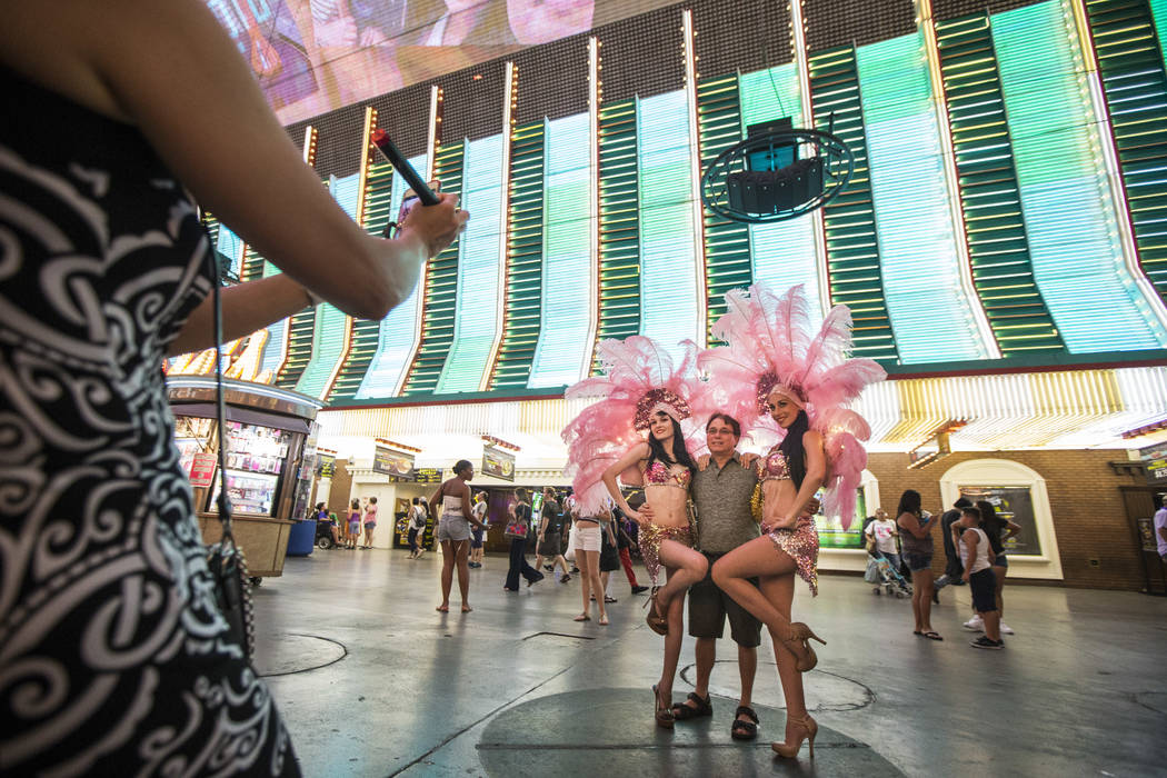 Felicia Vail, left, and Kelly Freesland, both of Showgirl Mafia, pose with Bruce Conrad of Illinois along the Fremont Street Experience in downtown Las Vegas on Wednesday, Aug. 2, 2017. Chase Stev ...