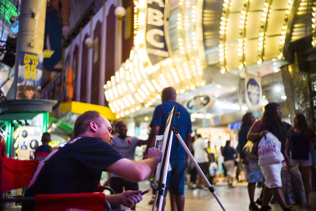 Artist Todd King works on a piece along the Fremont Street Experience in downtown Las Vegas on Wednesday, Aug. 2, 2017. Chase Stevens Las Vegas Review-Journal @csstevensphoto