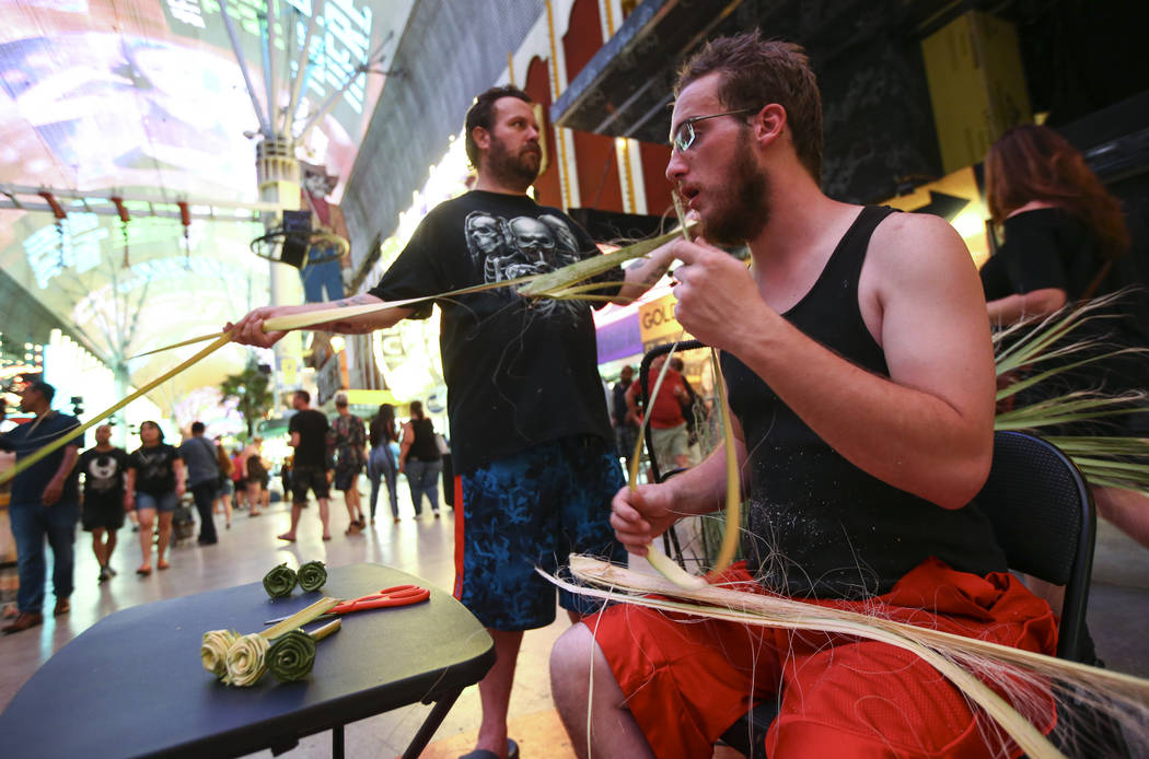 Roger, left, and Shaggy make items out of palm tree fronds along the Fremont Street Experience in downtown Las Vegas on Tuesday, Aug. 1, 2017. Chase Stevens Las Vegas Review-Journal @csstevensphoto