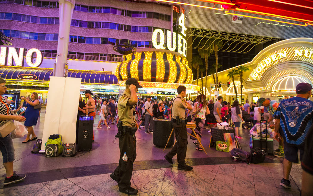 Security officers patrol along the Fremont Street Experience in downtown Las Vegas on Thursday, Aug. 3, 2017. Chase Stevens Las Vegas Review-Journal @csstevensphoto