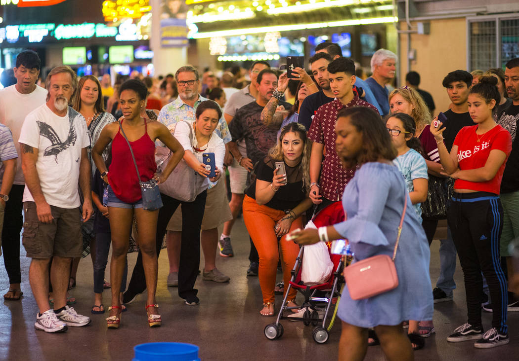 Tourists record and watch Bucket Nation, a group of buskers who drum on buckets, along the Fremont Street Experience in downtown Las Vegas on Thursday, Aug. 3, 2017. Chase Stevens Las Vegas Review ...