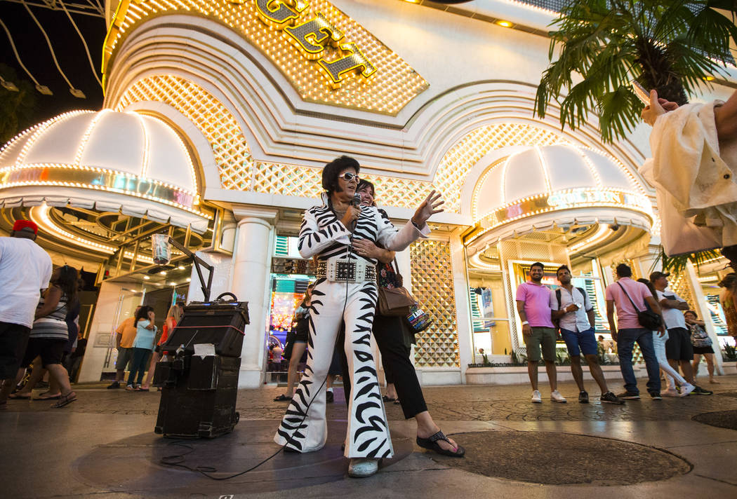 Chris Johnson, dressed as Elvis, poses for a photo with a tourist along the Fremont Street Experience in downtown Las Vegas on Tuesday, Aug. 1, 2017. Chase Stevens Las Vegas Review-Journal @csstev ...