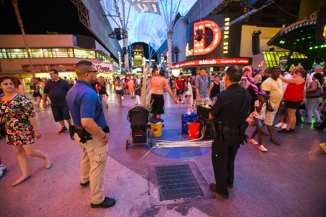 Busker Jason Mrdutt, center, is ticketed by Las Vegas city marshals along the Fremont Street Experience in downtown Las Vegas on Wednesday, Aug. 2, 2017. Mrdutt said he was eligible to stay in his ...
