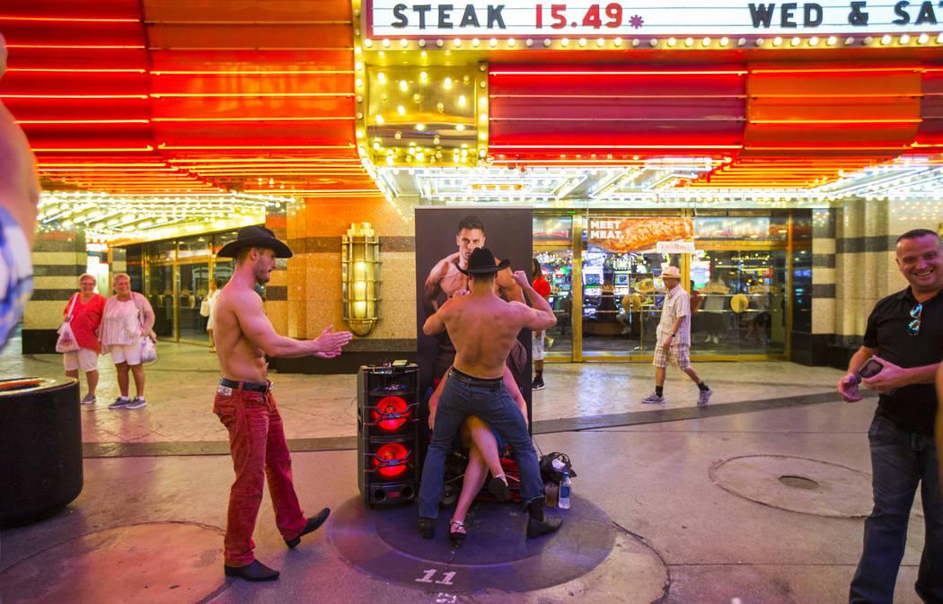 Busker Anthony Steel, center, entertains a tourist along the Fremont Street Experience in downtown Las Vegas on Thursday, Aug. 3, 2017. Chase Stevens Las Vegas Review-Journal @csstevensphoto