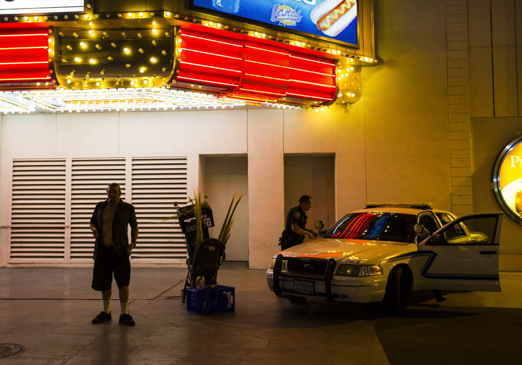 Busker Jason Mrdutt, left, waits to be ticketed by Las Vegas city marshals along the Fremont Street Experience in downtown Las Vegas on Wednesday, Aug. 2, 2017. Mrdutt said he was eligible to stay ...