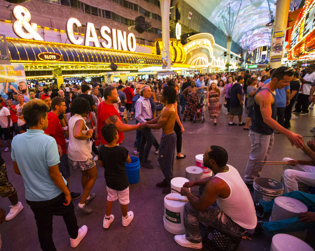 Buskers who go by the name Bucket Nation, referring the the buckets they drum on, mingle with tourists after performing along the Fremont Street Experience in downtown Las Vegas on Thursday, Aug.  ...